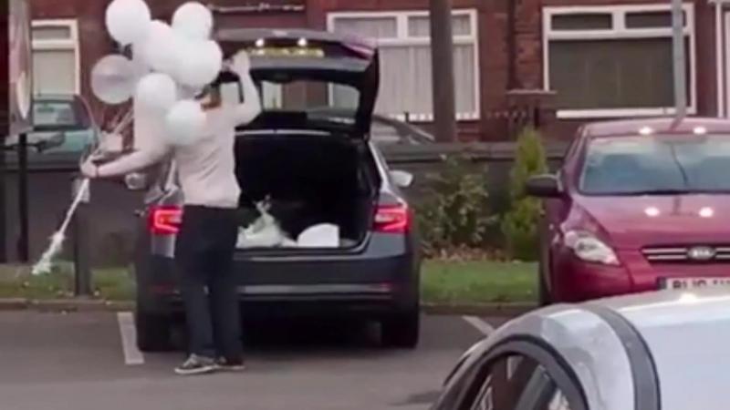 Смешно как парень пытается засунуть шарики в машину :) Funny how lad struggles trying to get a bouquet of balloons into car