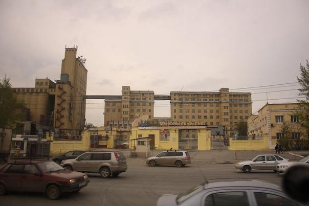 Слева на мелькомбинате элеватор на 8 этажей. На комбинате, основанном в 1937 году, работает примерно 400 человек. Крупнейший в Новосибирской области зерноперерабатывающий комплекс, на «нормальных» мощностях занимает 10 % рынка переработки зерна. Когда фоткал, завод находился в состоянии банкротства. И вообще он постоянно банкротится.  Комбинат — это объединение разных производственных процессов, нескольких «мелких производств».