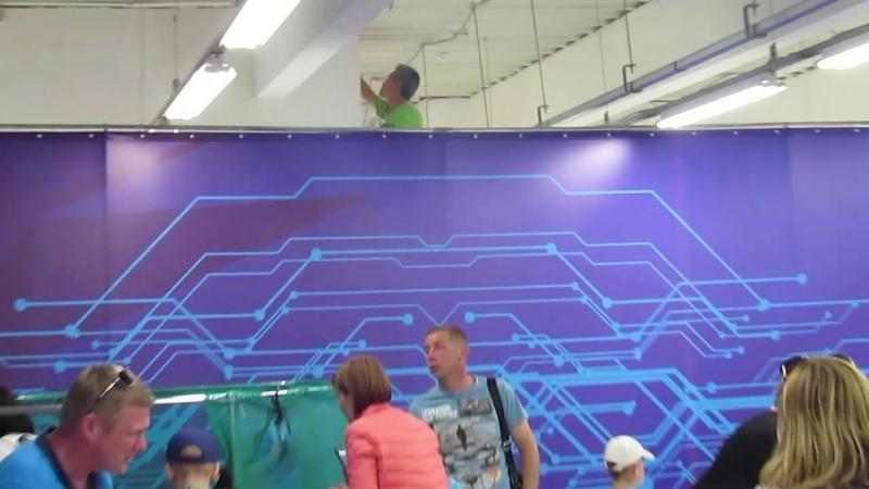 Чувак шпаклюет стену. Выставка роботов идет своим чередом.