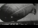 Gunner in military biplane shoots down a large blimp in the air over Chicago Stock Footage