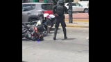 The cop is fighting a motorcyclist. Police officer vs moto rider