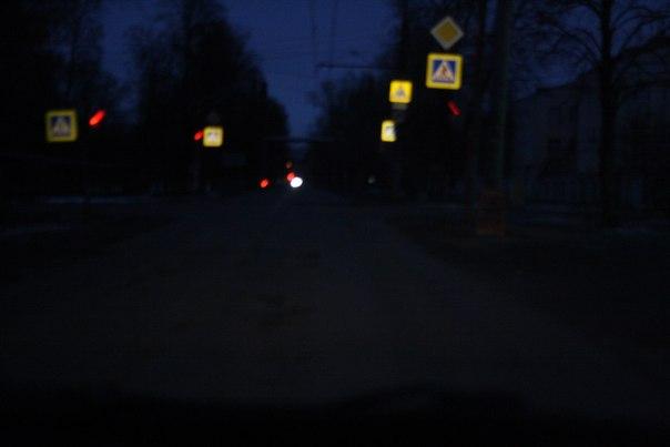 Как только водители не сходят с ума от этого? Действительно же знак хуже видно из-за этого светоотражения.  Но главное: если тут появится чёрная тень — её не заметишь, потому что это бешенство слепит, а фонарей вообще никаких не горит.  Правильно — подсветить пешехода, тогда их не будут давить.  14 ноября 2017