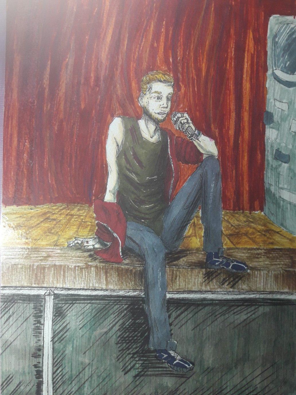 На краю сцены, на фоне красного сценического задника, сидит в свободной позе русоволосый парень и что-то рассказывает в микрофон. Правую ногу он свесил со сцены вниз, левую согнул в колене, оперевшись на неё локтем левой руки, в которой он и держит микрофон. Правой рукой и ступнёй левой ноги он опирается на напольное покрытие сцены. Одет в тёмно-зелёную футболку без рукавов, спущенную с плеча красную толстовку на молнии, серые штаны, обут в синие кроссовки.