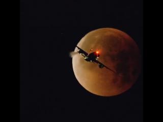 Авиалайнер Airbus A350 пролетает на фоне затмившейся Луны 31 января 2018 года