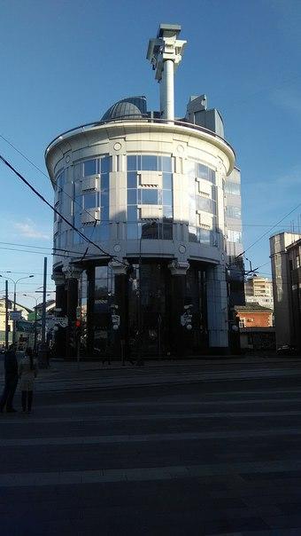 Какое-то поехавшее зданице: колонны на крыше, черные колонны с белым ордером внизу, остекление.  Тяжеленные конструкции возле легчайших.