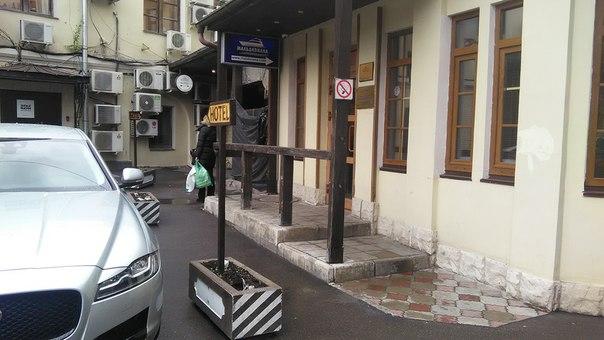 Обычный Московский двор: всё заставлено автомобилями, деревянные поручни, барьеры для авто превратили в вазоны, указатели, куча кондеев и водостоки.
