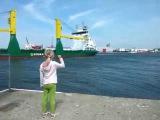 Маленькая девочка, стоящая на пристани, просит посигналить проплывающий корабль