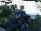 Сережа играет на гармони и поет