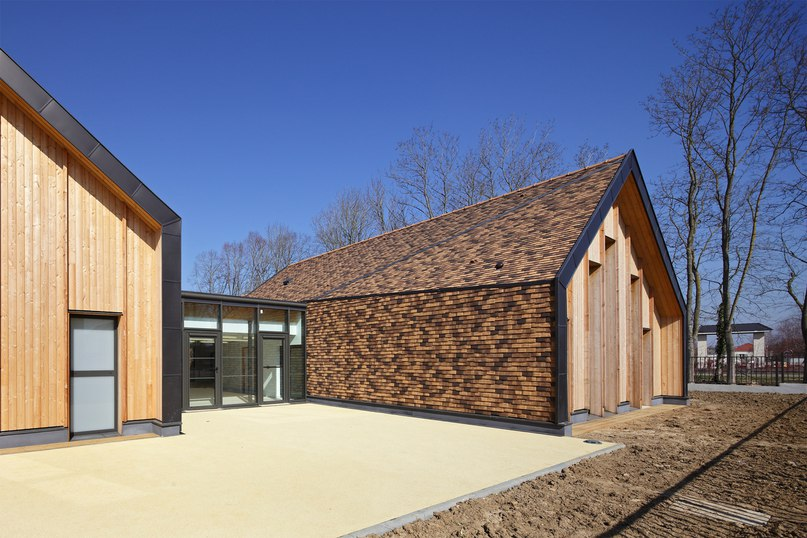 Brown ceramic shingles cover Nomade Architectes' village-inspired