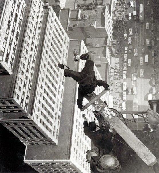 Мужчина балансирует на доске на краю крыши