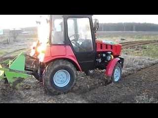 Трактор Беларус 320 (МТЗ) с почвенной фрезой в процессе работы