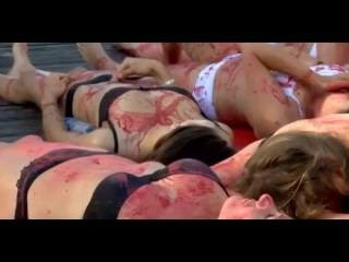 Half-naked animal rights activists brand each other with hot irons in the street during shocking