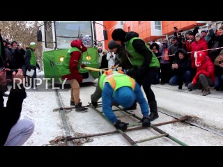Россия: Женщина оставляет толпы в страхе, потянув два трамваи, заполненные пассажирами.