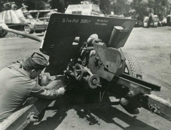 американец осматривает захваченную у немцев трофейную пушку Зис-2. На щите трафаретом написано немецкое обозначение орудия.
