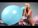 Girl blow to pop a big blue balloon