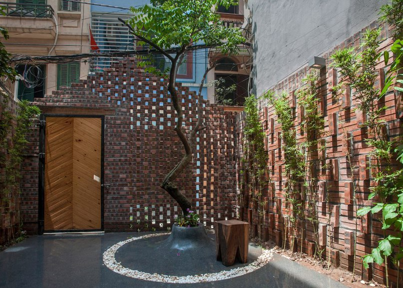 Perforated brick gable screens courtyard in front