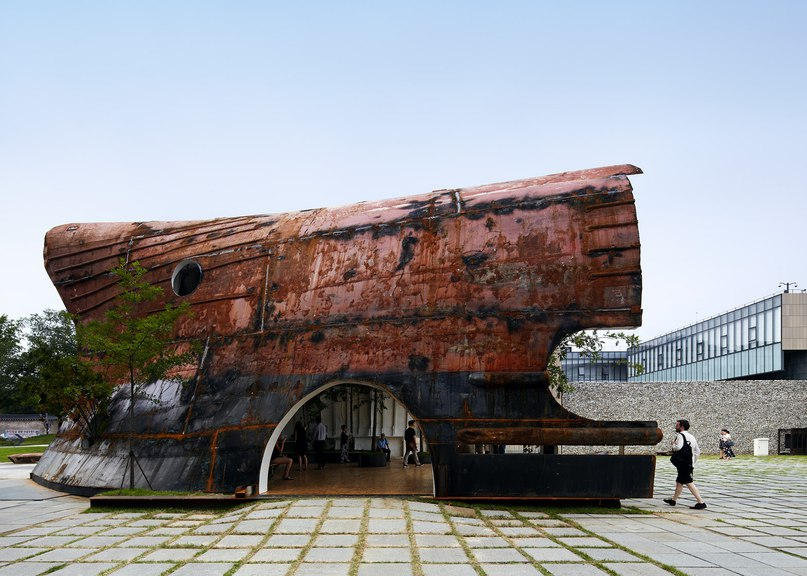 Rusty ship transformed into cavernous pavilion for