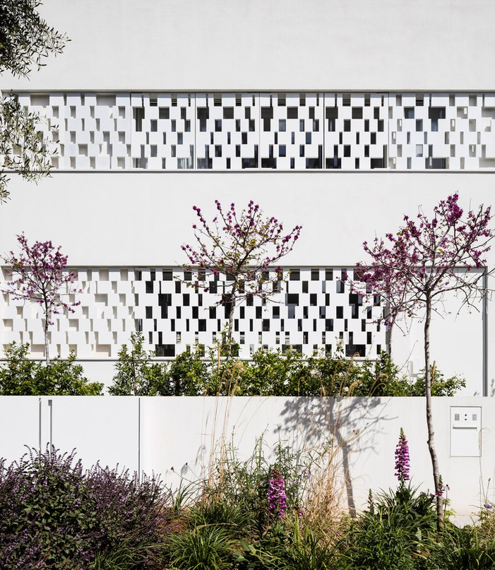 Perforated shutters create geometric facade for Pitsou