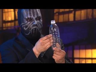 Засовывает телефон в бутылку