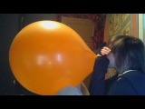Emo girl blows up a giant orange balloon until it pops