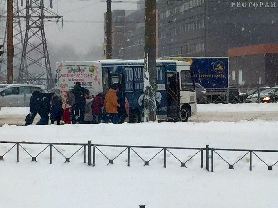 Пассажиры толкают застрявшую вснегу маршрутку на промышленном
