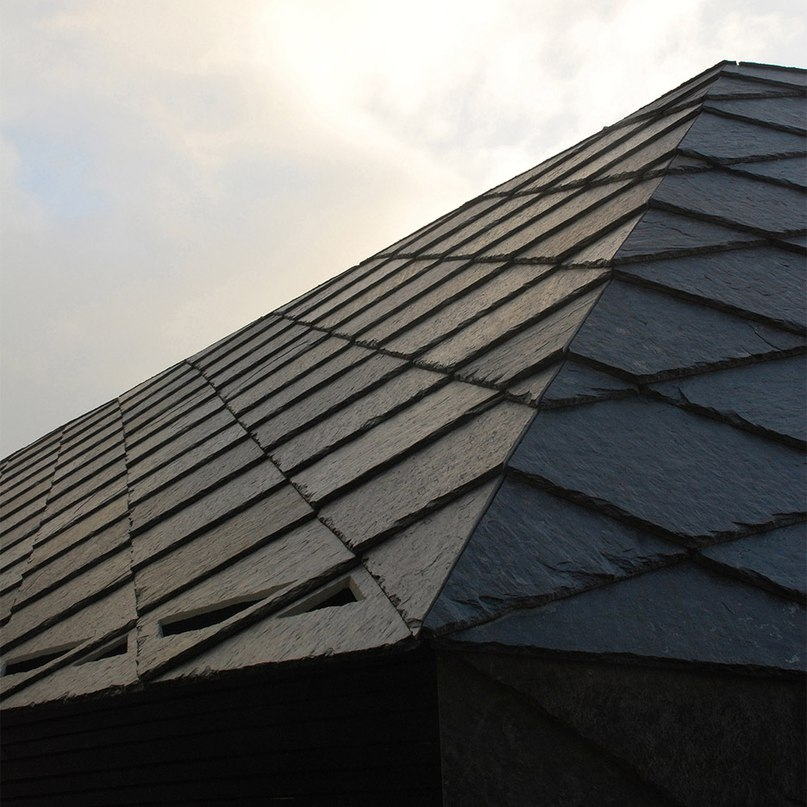 Dark grey slates create diamond-patterned facades for