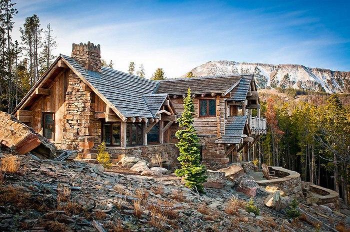 Красивый бревенчатый дом в окружении невысоких гор,