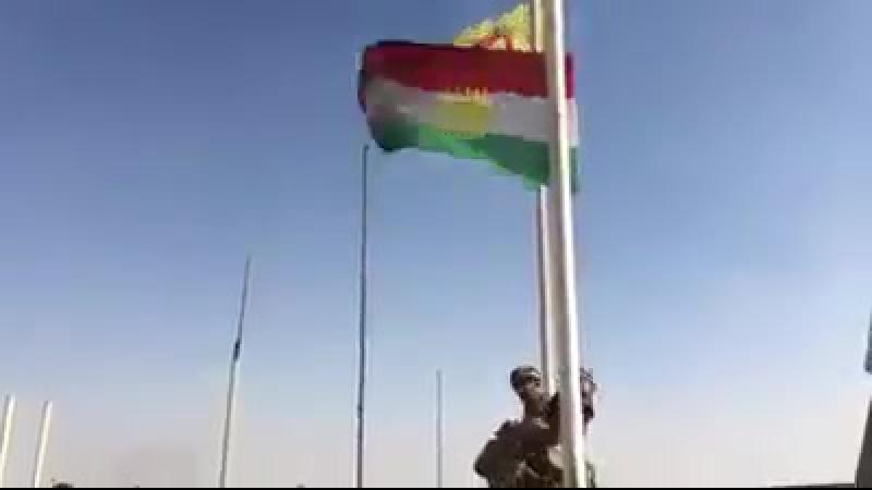 Иракцы снимают флаг курдской пемшерги в Киркуке