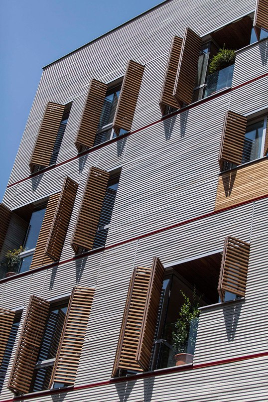 Ayeneh Office gives Tehran apartments a textured facade with ridged granite and slatted timber