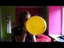 Scared girl blowing up a balloon popping to shreds