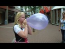 Cute girl blowing up a pretty balloon until it pops outside