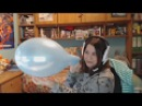 Gamer girl blow to pops a blue balloon
