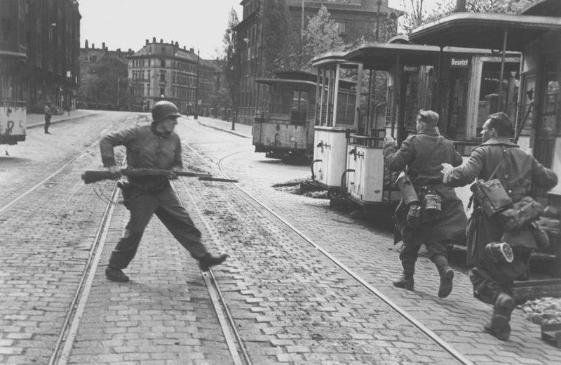 Солдат 2-й пехотной дивизии США и немецкие военнопленные в городе Лейпциг.