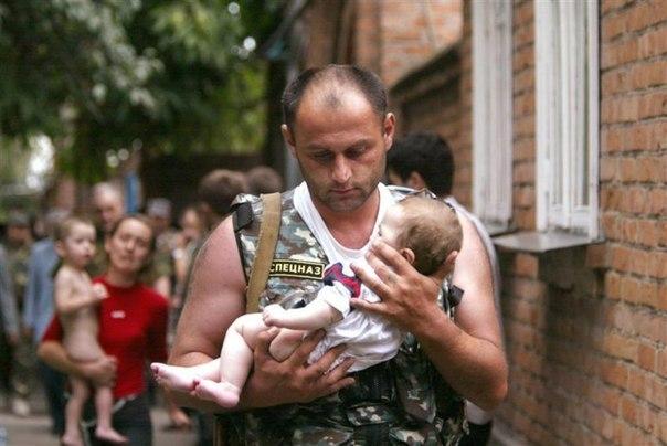 Российский спецназовец несет ребенка