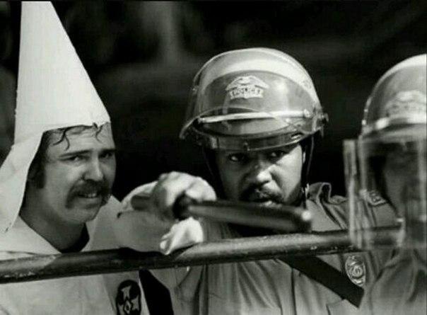 Чёрный полицейский защищает членов Ку-Клукс-Клана от протестующих,
