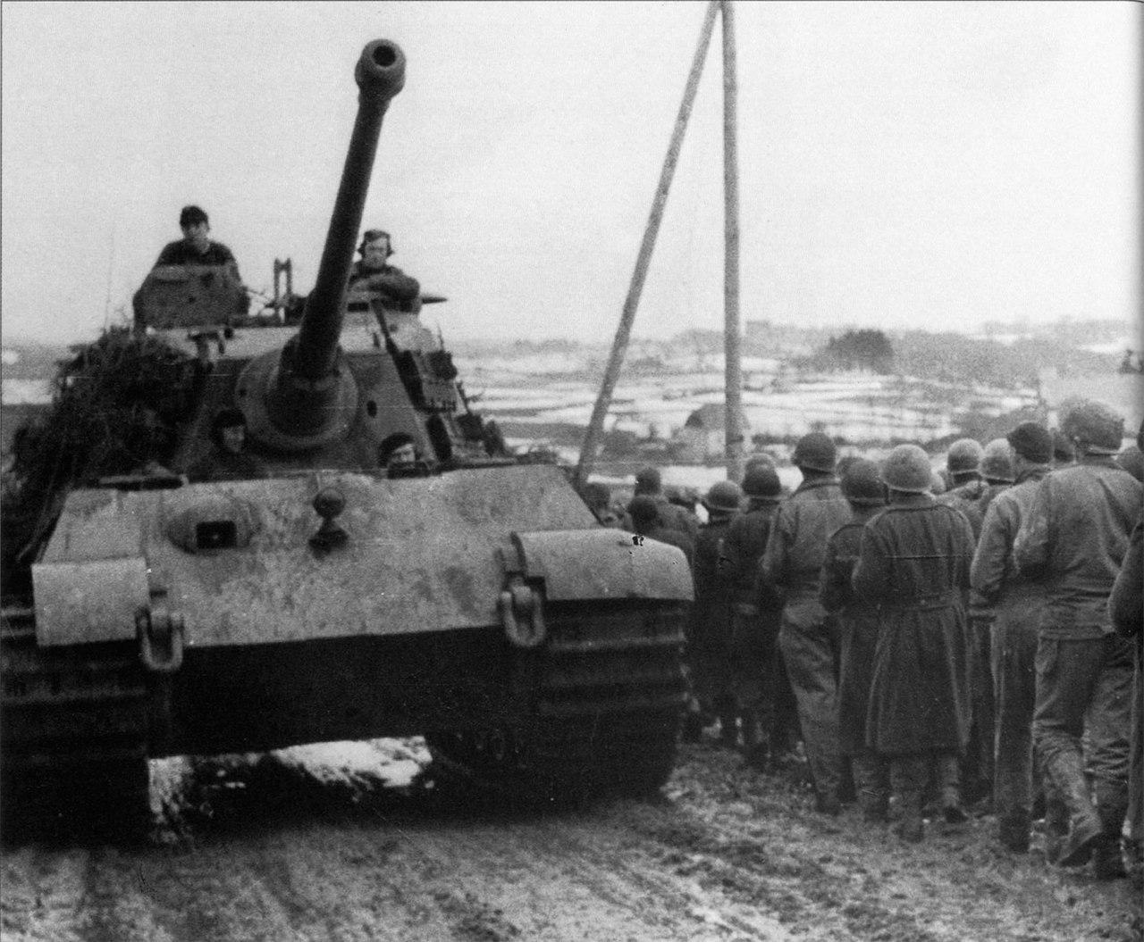 Тяжелый танк Pz.Kpfw. VI Ausf. B «Королевский Тигр» 501-го тяжелого танкового батальона СС, входивший в состав боевой группы Пайпер , едет вдоль колонны пленных солдат 99-й пехотной дивизии США в Бельгии. 1944 г.