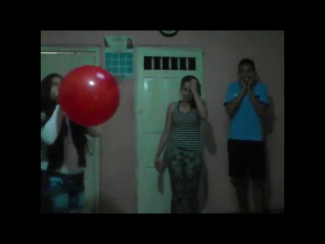 Girl blows to pop red balloon with scared guy and girl watching