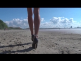 Longs legs in metal spike heels walking in sand Sandy Spikes Trailer