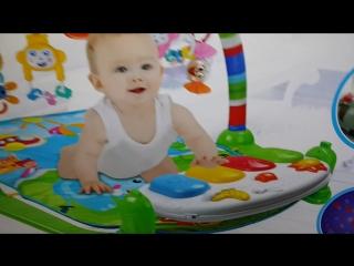 Игровой коврик для малыша с пианино, дугой и игрушками.