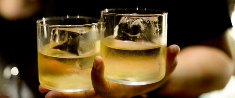 два бокала виски со льдом в одной руке официант бармен подаёт коктейль