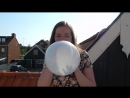 Girl blows up a white balloon until it pops on a