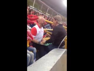 Слепой мужчина с помощью своего друга наслаждается игрой любимой футбольной команды
