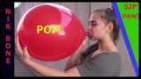 Susanne pustet einen roten Luftballon auf und setzt sich drauf, dabei f