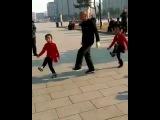Chinese grandpa and two girls shuffle dance