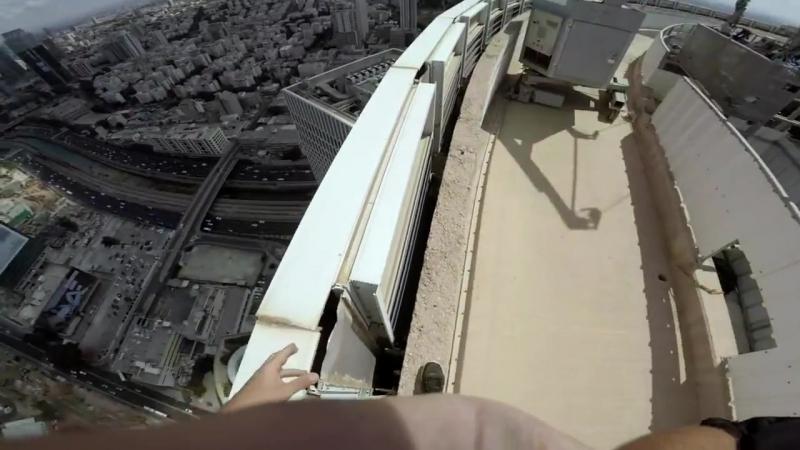 Стойка на руках на краю небоскреба в Тель Авиве