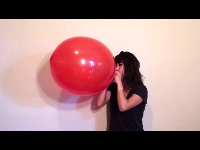 Cute girl blow to pop large punch balloon