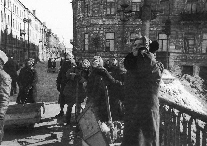 Женщины, занятые уборкой ленинградских улиц, наблюдают за воздушным боем над городом. Весна 1943 г.