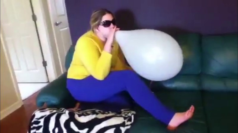 Cool sunglasses girl blow to pops white balloon