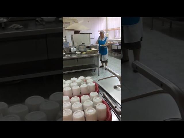 Работница школьной столовой накладывает котлеты голыми руками