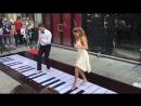 Пара молодой человек и девушка играют мелодию Розовая Пантера на напольном пианино фортепиано